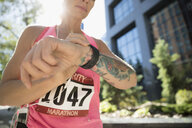 Tattooed female marathon runner checking smart watch in urban park - HEROF23242