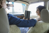 Smiling woman with digital tablet photographing boyfriend driving car - HEROF23245