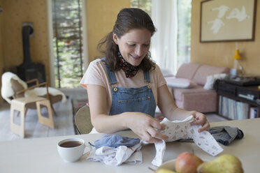 Pregnant woman folding baby clothes at dining table - HEROF23260