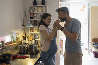 Pregnant woman feeding husband in kitchen - HEROF23263