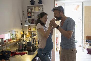 Pregnant woman feeding husband in kitchen - HEROF23263