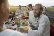 Smiling man eating and drinking, enjoying garden party dinner - HEROF23272