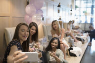 Smiling bridesmaid friends and bride-to-be taking selfie in nail salon - HEROF23305