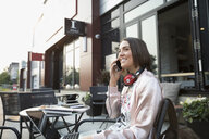 Smiling brunette woman with headphones talking on cell phone at laptop at sidewalk cafe - HEROF23308
