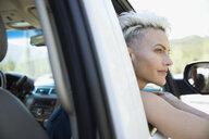 Serene woman leaning out car window, enjoying road trip - HEROF23326