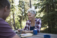 Smiling couple playing cribbage at campsite picnic table in woods - HEROF23329