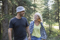 Smiling couple holding hands, hiking in summer woods - HEROF23332