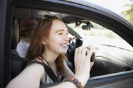 Smiling woman using digital camera in car, enjoying road trip - HEROF23341