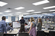 Teacher with whiteboard leading chess club lesson in library - HEROF23356