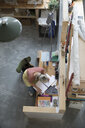 View from above female artist sketching in notebook at desk in art studio - HEROF23362