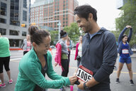 Wife helping smiling husband put on marathon bib on urban street - HEROF23365