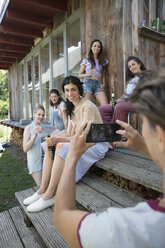 Woman with camera phone photographing friends drinking beer on cabin patio - HEROF23374