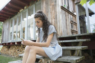 Young woman texting with cell phone on wood cabin steps - HEROF23377