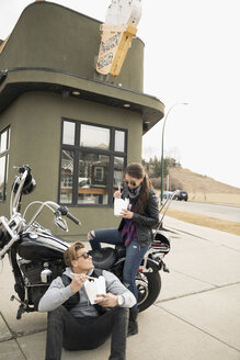 Biker couple eating take out Chinese food at motorcycle in parking lot - HEROF23479