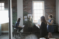 Architects meeting, hanging blueprints on brick wall in loft office - HEROF23485