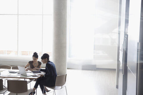 Businesswomen working at laptop in conference room meeting - HEROF23503