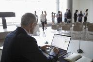 Businessman working at laptop, preparing conference presentation - HEROF23533