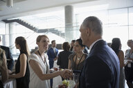Business people handshaking, networking and eating at conference - HEROF23539