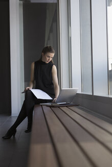 Businesswoman working at laptop on office bench - HEROF23587