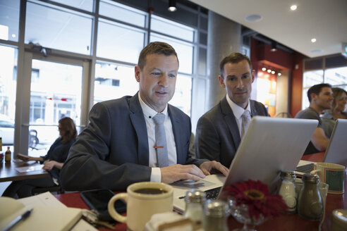 Businessmen working at laptops at diner counter - HEROF23596