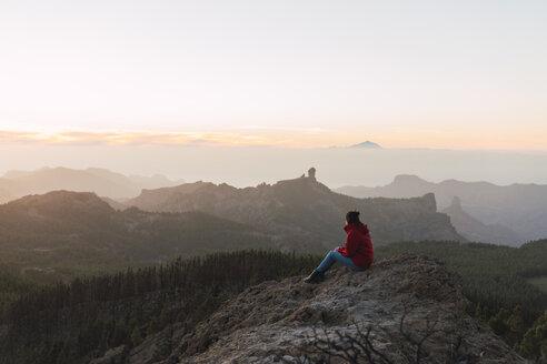 Spain, Gran Canaria, Pico de las Nieves, woman sitting on rock looking at view - KKAF03119