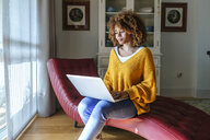 Young woman sitting on chaiselongue using laptop at home - KIJF02272