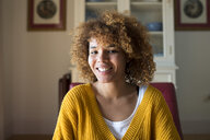 Portrait of smiling young woman with curly hair at home - KIJF02275