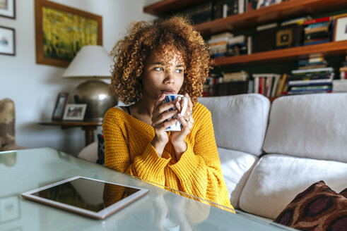 Young woman with curly hair holding mug at home - KIJF02281