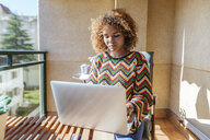 Young woman with curly hair sitting on balcony using laptop - KIJF02290
