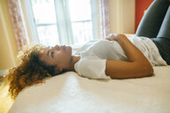 Thoughtful young woman with curly hair lying in bed at home - KIJF02305