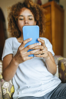 Close-up of young woman sitting in armchair at home using cell phone - KIJF02314