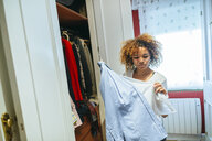 Young woman with curly hair at home looking at clothing in her wardrobe - KIJF02320