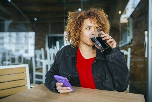 Young woman with cell phone drinking cola at a bar - KIJF02323