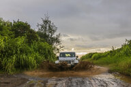 USA, Hawaii, Kauai, off-road vehicle on muddy dirt road, puddle - FOF10441