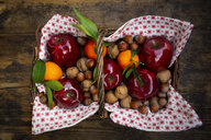 Wickerbasket of red apples, tangerines, hazelnuts and walnuts - LVF07788