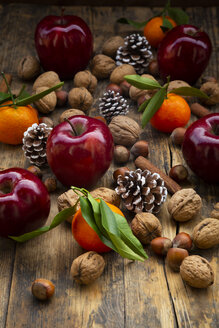 Red apples, tangerines, hazelnuts, walnuts, cinnamon sticks and pine cones on dark wood - LVF07791