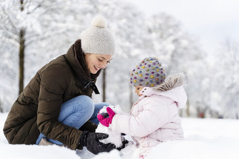 Happy mother playing with daughter in winter landscape - DIGF05883