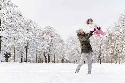 Happy father playing with daughter in winter landscape - DIGF05892
