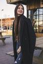 Portrait of smiling teenage girl wearing black coat - ACPF00467