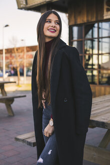 Portrait of smiling teenage girl wearing black coat - ACPF00467