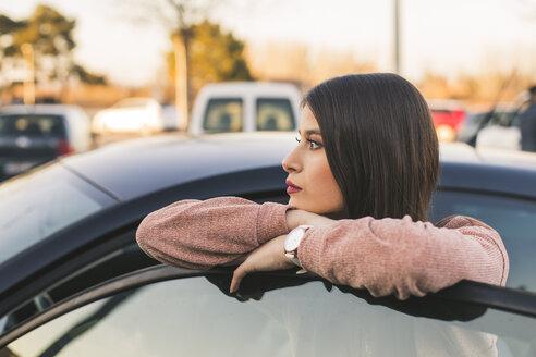 Teenage girl leaning on car door looking at distance - ACPF00470