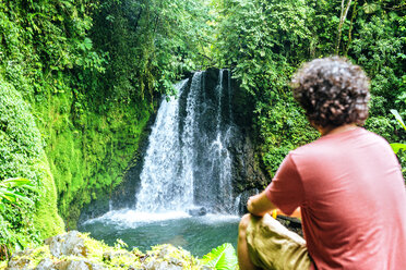 Costa Rica, sitting man looking at a waterfall - KIJF02326