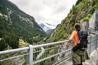 Switzerland, Valais, woman on a hiking trip from Blatten to Riederalm on a dam wall - DMOF00104