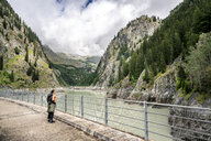 Switzerland, Valais, woman on a hiking trip from Blatten to Riederalm on a dam wall - DMOF00107
