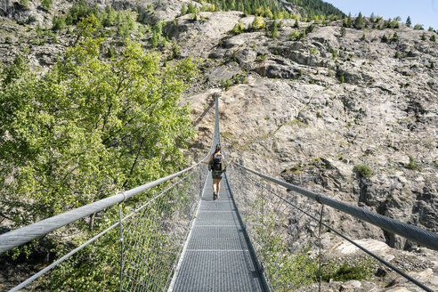Switzerland, Valais, woman on a hiking trip in the mountains from Belalp to Riederalp on a swinging bridge - DMOF00116