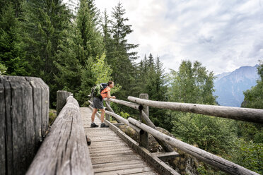 Switzerland, Valais, woman standing on a wooden bridge during a hiking trip on the Massaweg in the mountains - DMOF00119