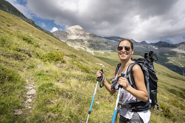 Switzerland, Valais, portrait of happy woman on a hiking trip in the mountains towards Foggenhorn - DMOF00131