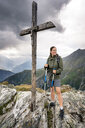 Switzerland, Valais, woman on a hiking trip in the mountains at Foggenhorn summit - DMOF00134
