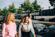 Cheerful friends walking on street by cars in city - MASF11410