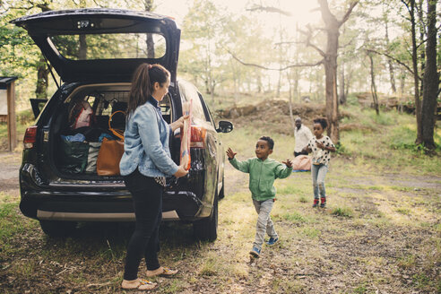 Kids helping mother unloading luggage from car trunk at public park - MASF11422
